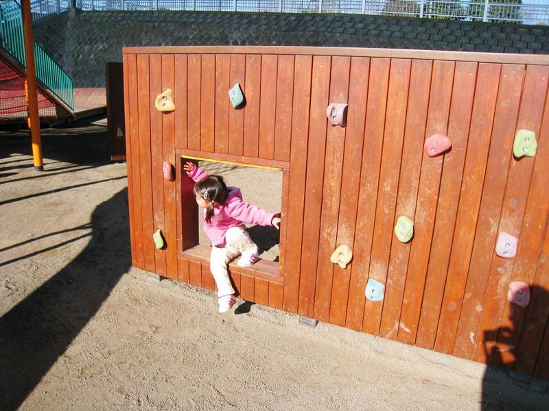 ボルダリングのついた茶色い壁の四角い穴にいる子供