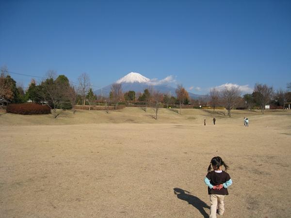 富士山と芝生を歩く女の子