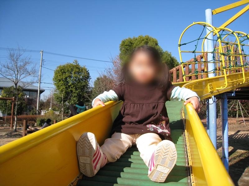 ローラ滑り台を滑る子供