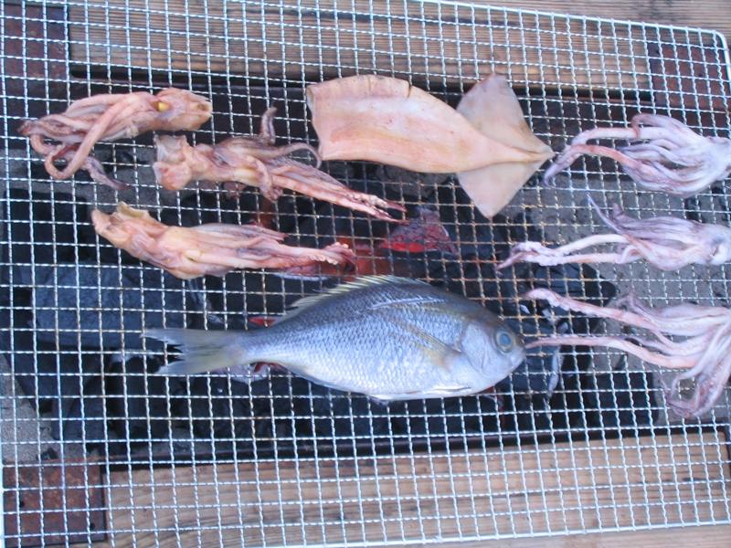 イカや魚が網で焼かれている