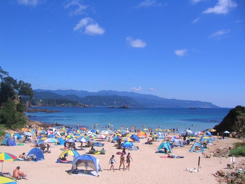 青い空と海、砂浜には多くのパラソルと人々