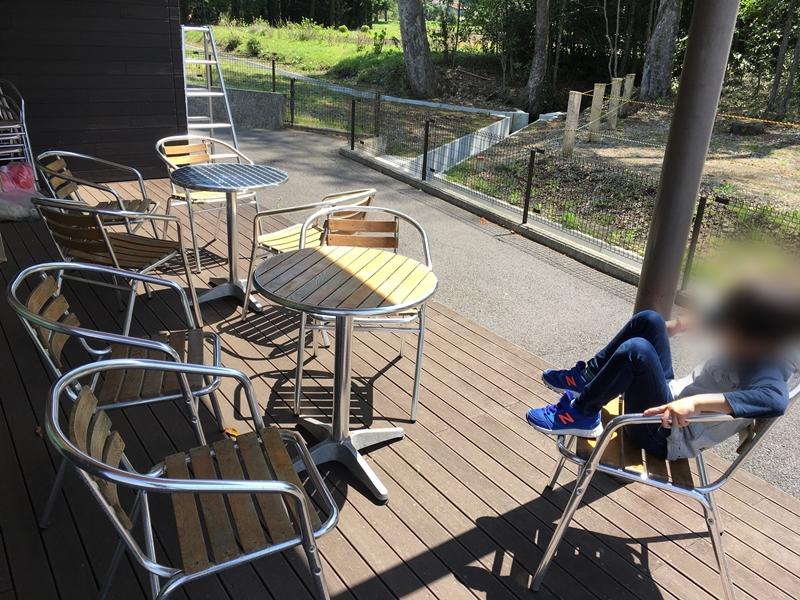 テラスにテーブルと椅子座る子供