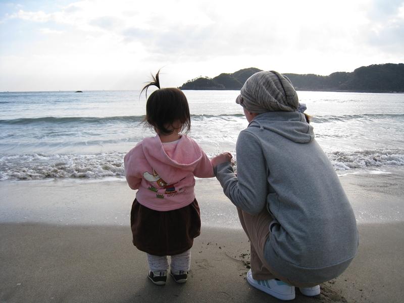 親子が手をにぎり空と海を見ている