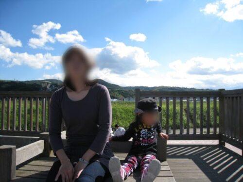 狩野川リバーサイドパークで、青空の下に座っている女性と子