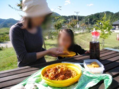 狩野川リバーサイドパークで座って焼きそばを食べている子と女性