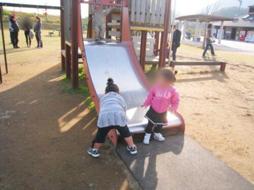 狩野川リバーサイドパークの滑り台の前に立つ子供2人