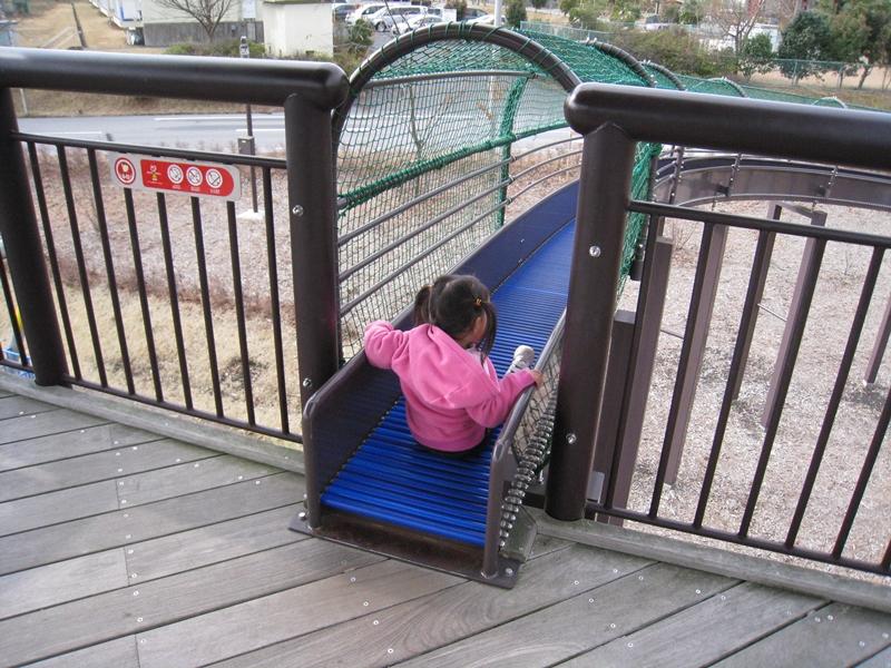 青いローラーすべり台を女の子が滑ろうとしている