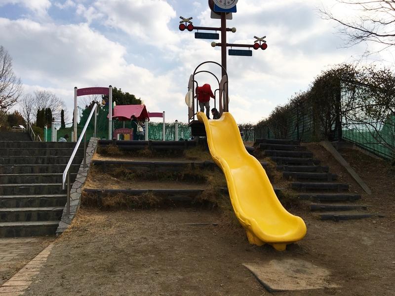 黄色いすべり台を滑ろうとしているこども