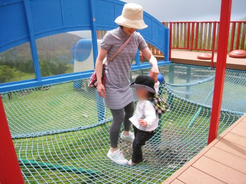 モーモーキッズランドのネットの上で遊ぶ子供と女性