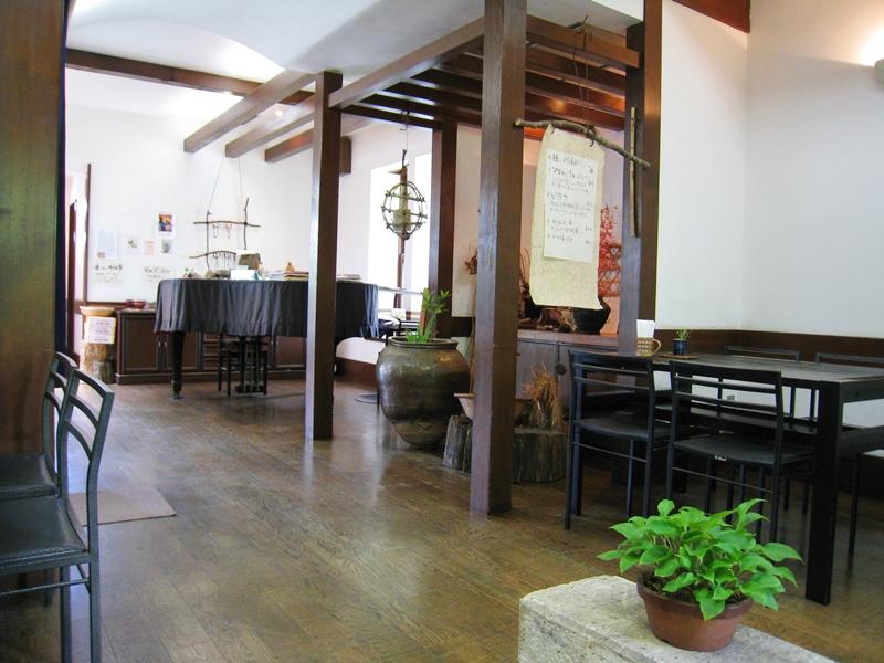黒のテーブルや椅子と床奥にピアノがある