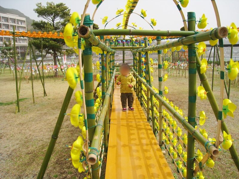 黄色い風車の中を歩く子
