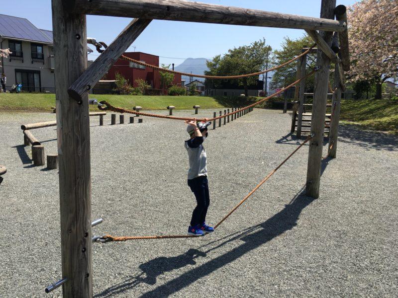 ロープの遊具につかまり渡っている子供