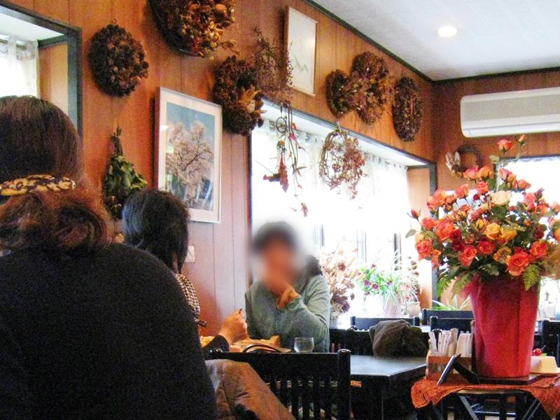 テーブルに人がいる壁にはリースや絵がかけられている