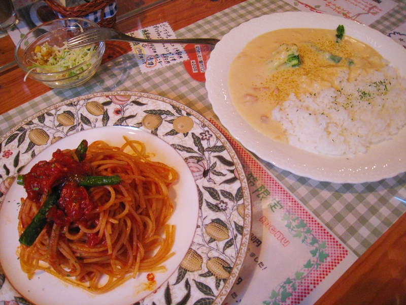 左にスパゲティ右に白いカレー上にサラダ