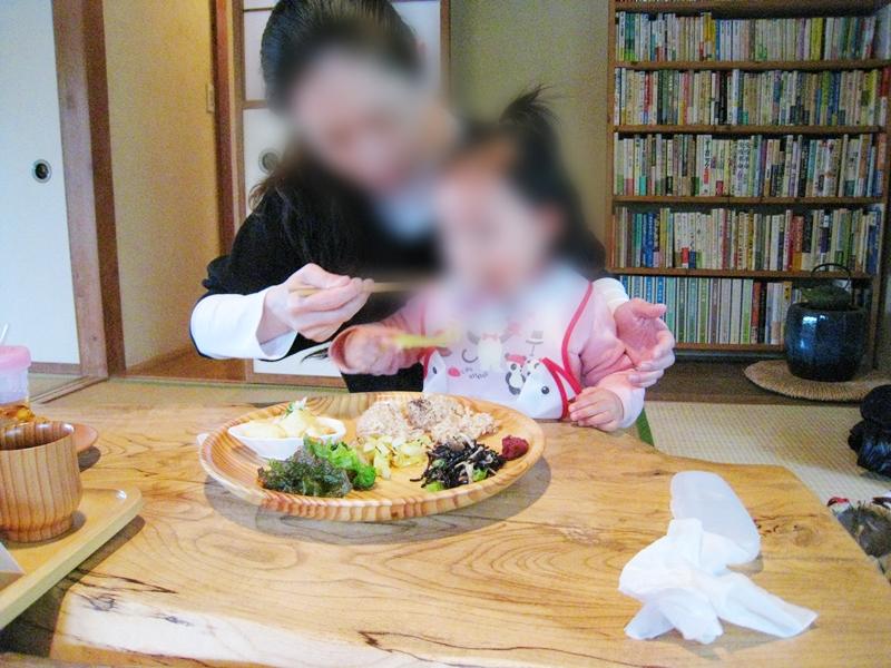 一緒にご飯を食べる女性と子供後ろに本棚