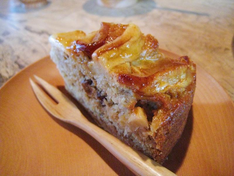木の皿にケーキと木のフォークが乗せられている