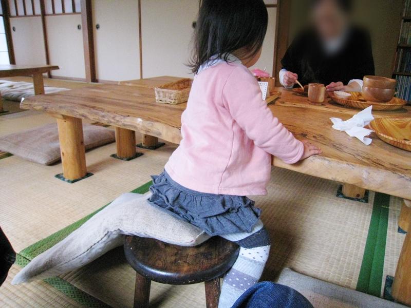 椅子に座るこどもとテーブルを挟んでランチする大人