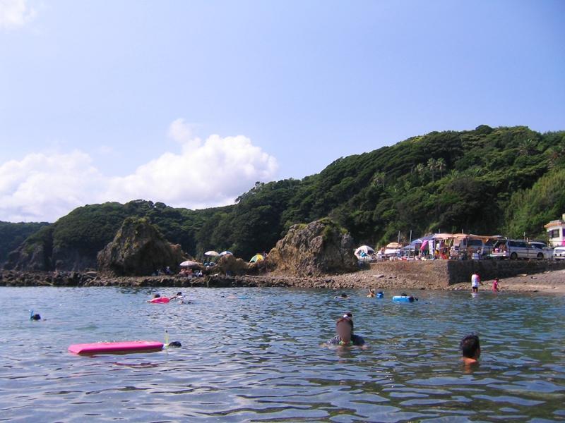 海で泳ぐ人と背景に山と青空