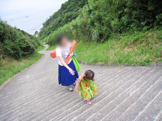 シュノーケリングできる九十浜の上り坂をうつむきながら歩く子供と女性