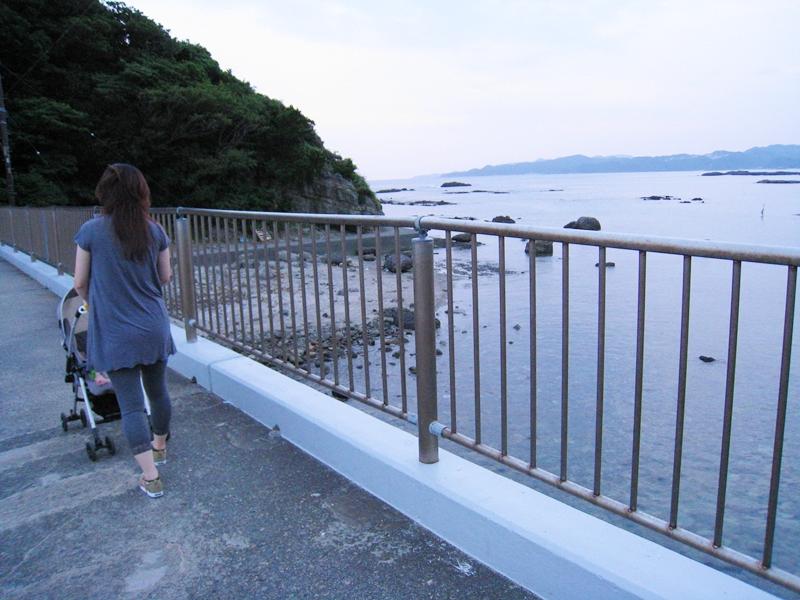 柵がある歩道を歩く女性の後姿と海