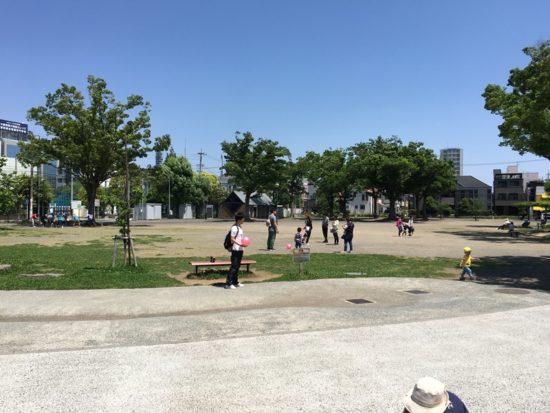 森下公園の広場に立つ人々、青空と木々