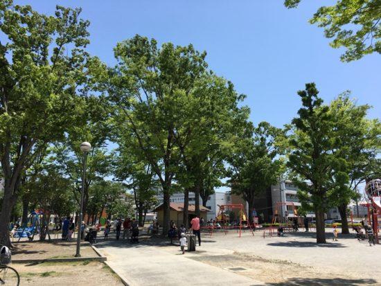 緑の高い木々と森下公園を歩く人