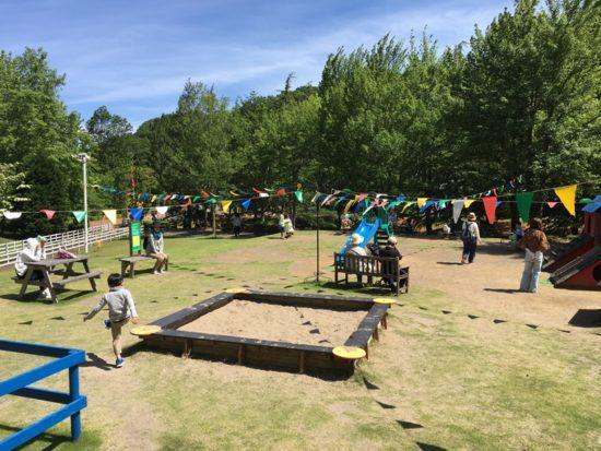 虹の郷の広場に砂場や遊具があり子供が遊んでいる