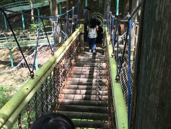 虹の郷の木のつり橋を子供がわたっている