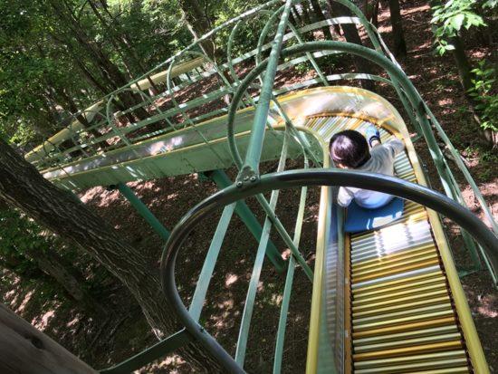 虹の郷のローラー滑り台を滑る子供