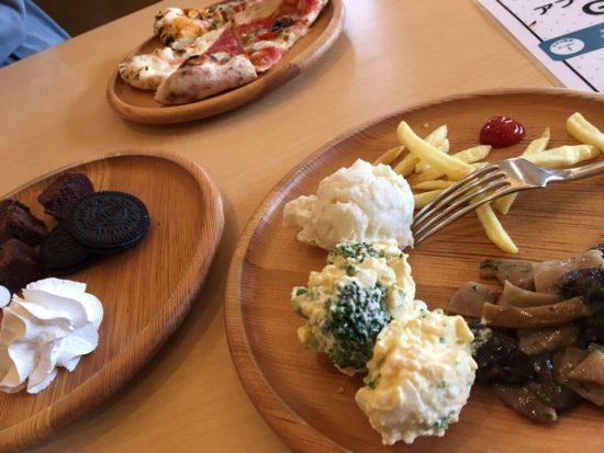 OMOCHAのテーブルに丸い皿が3つと食べ物が乗せられている