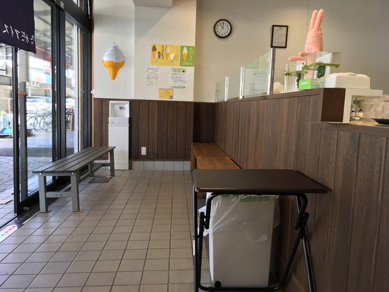 木のカウンターと椅子やテーブルが置かれている