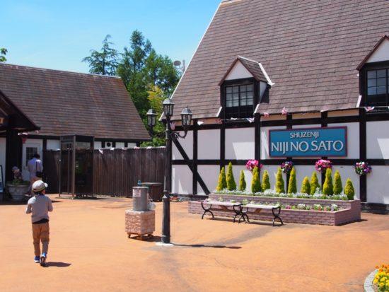 虹の郷のNIJINOSATOと書かれた建物と歩く子供