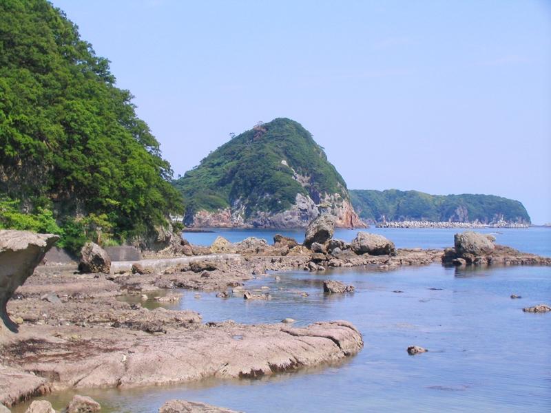海沿いに岩場が続く、奥に小さな山がみえる