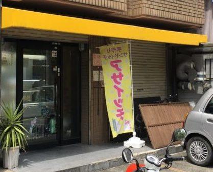 ビルの1階にアサイッチの黄色い幟その前に車とバイクが停まっている