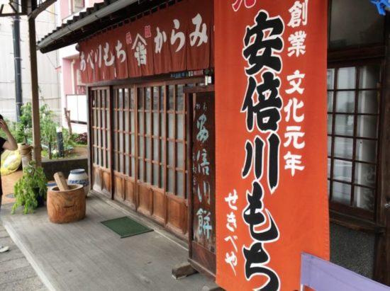 赤い安倍川もちの幟とのれんがかかった石部屋(せきべや)の店舗
