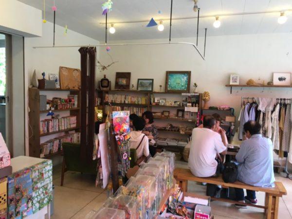 壁に本棚が並び、その前で椅子に座っている人々