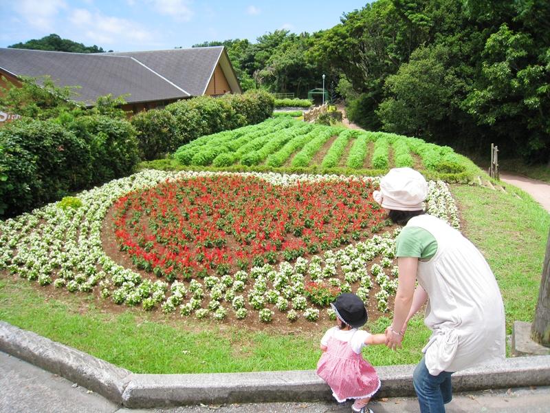 ハート型に植えられた植物の前に女性と子供が立っている
