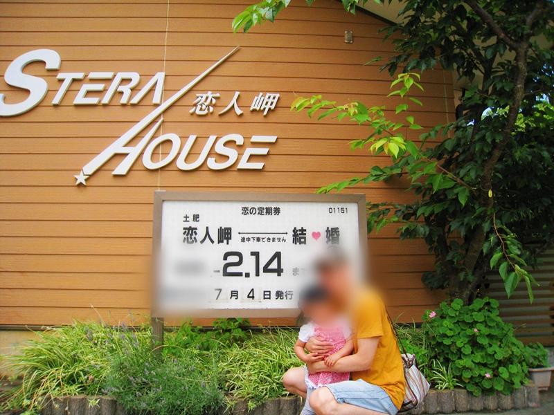 恋人岬、2.14と書かれた看板の下に座る親子