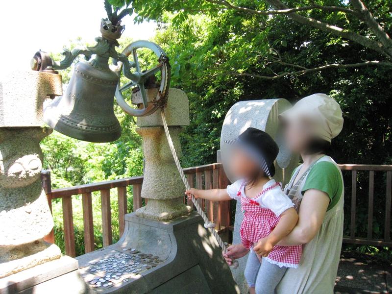 女性に抱っこされた子供が鐘を鳴らそうとしている