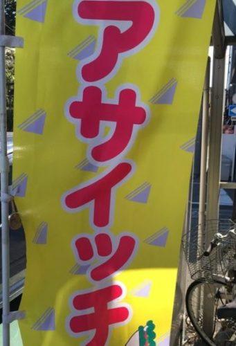 アサイッチと書かれた黄色い幟、横に自転車