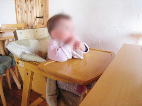 伊豆でランチできるしいのき山の木のベビーチェアに座る子供