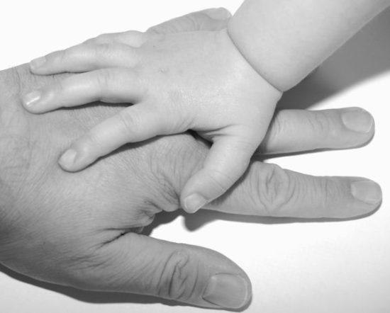 大人の手の上に子供の手が重なっている