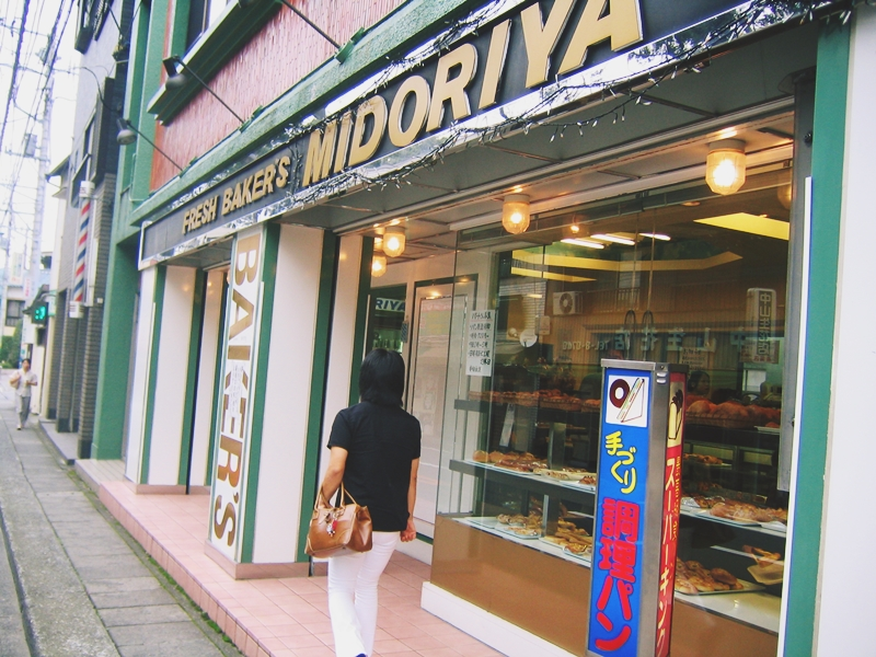 MIDORIYAの文字と店、その前を歩く人