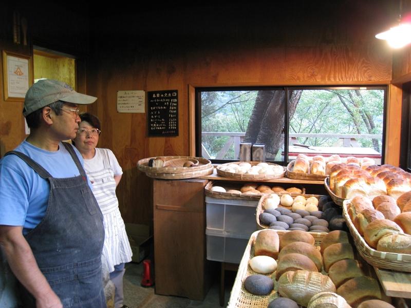 パンの前に立つ帽子を被る男性と女性