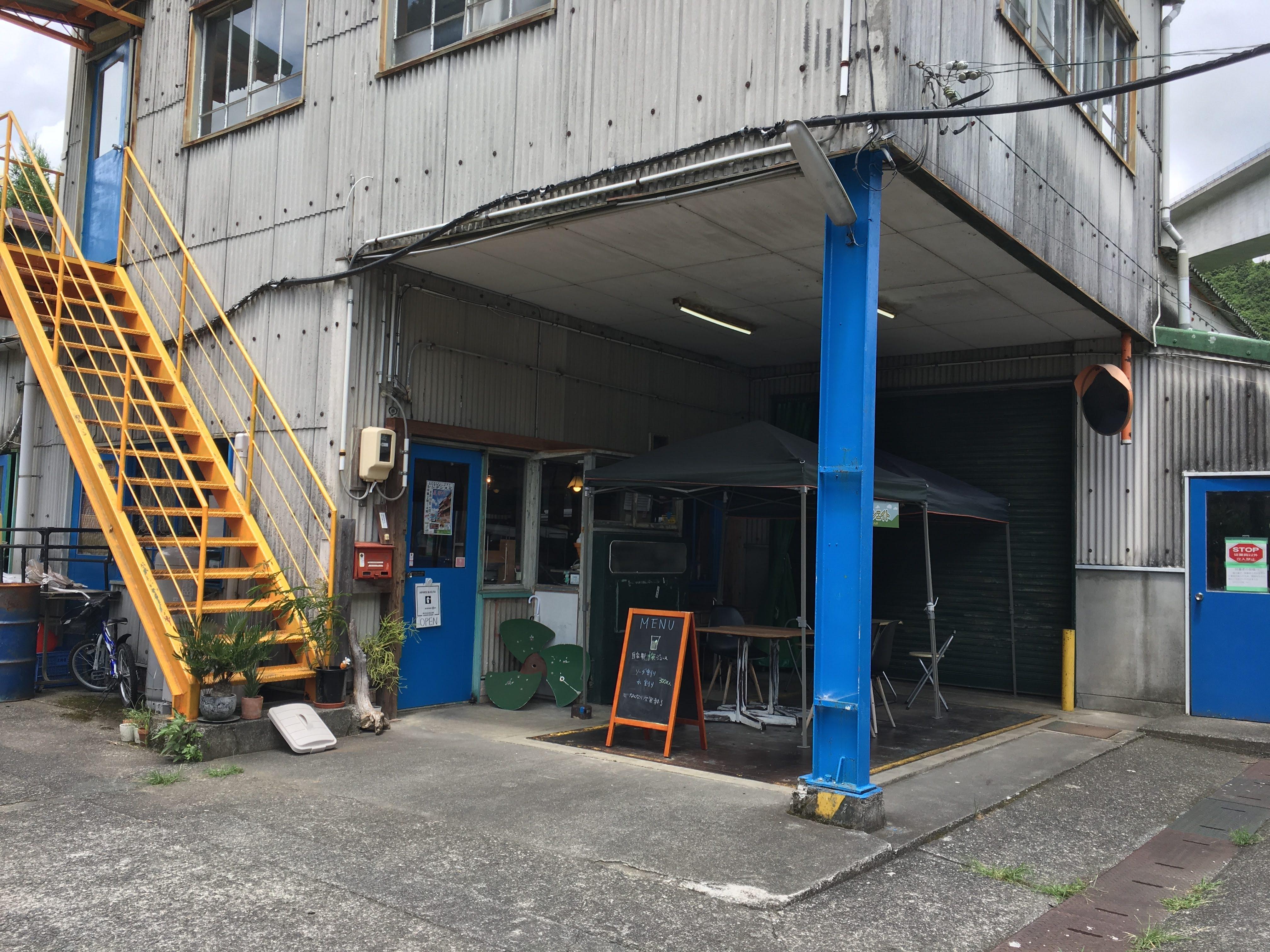 コンクリートの建物に青い柱と黄色い階段がある