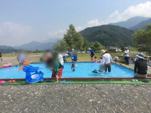 うしづま水辺の楽校の水色のシートのプールで遊ぶ親子