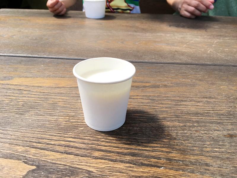 白い紙コップに入った白い液体が木のテーブルに置かれている