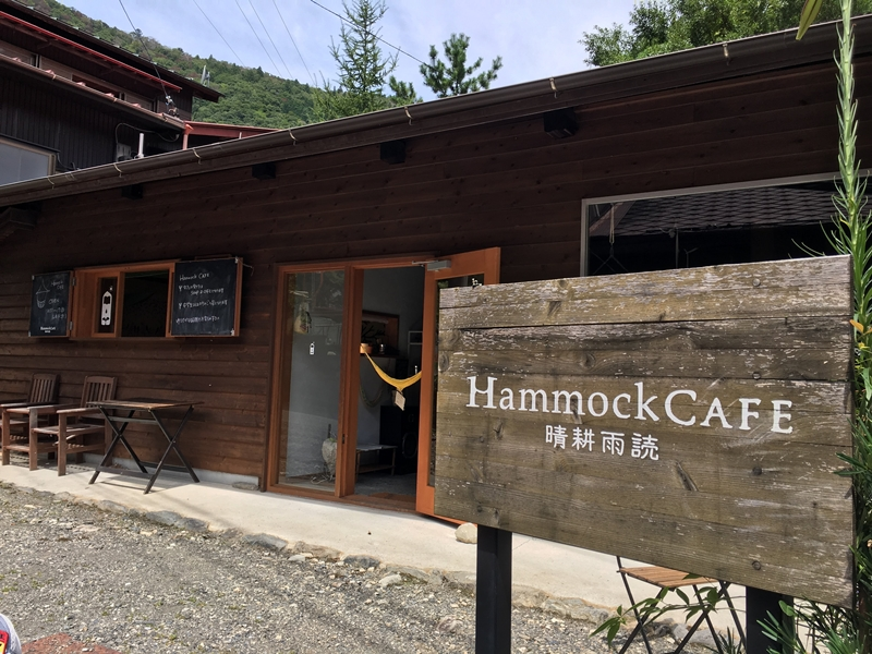 Hnmmockcafeと書かれた木の看板と後ろに建物