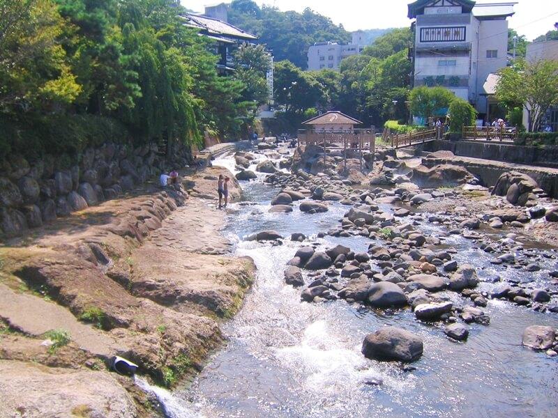 岩のある川と奥に建物がみえる