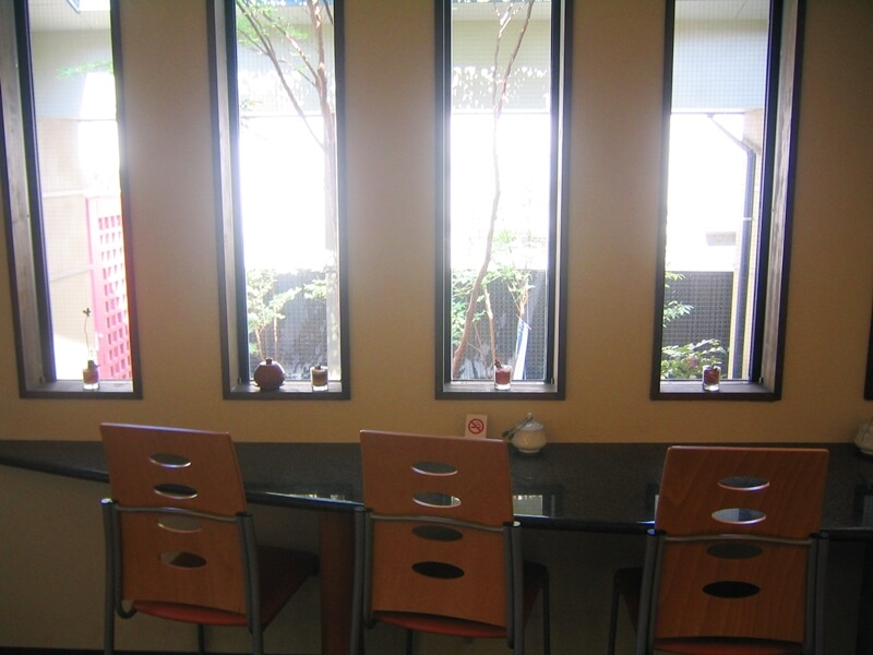 縦長の窓が4つ並び、手前にテーブルと椅子